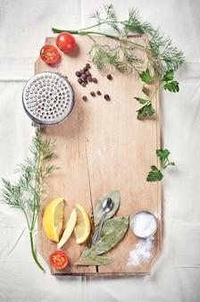 Vis koken: keukengerei, specerijen en kruiden voor het koken van vis, op houten snijplank, met ruimte voor tekst