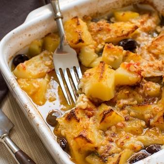 Vis met aardappelen en olijven gekookt in de oven in een kleine braadpan close-up