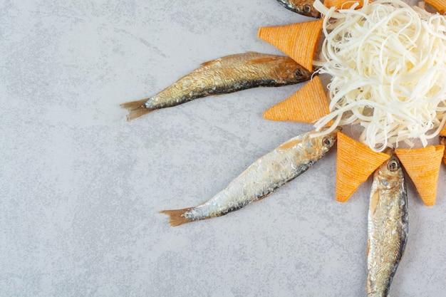 Vis met kaas en gele chips op grijs.
