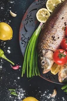 Vis met kruiden en groenten geserveerd met citroen