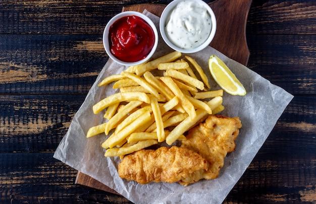 Vis met patat op een houten achtergrond. brits fastfood. recepten. snack tot bier. engelse keuken.