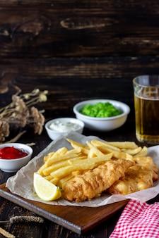 Vis met patat op houten. brits fastfood. recepten. snack tot bier. engelse keuken.