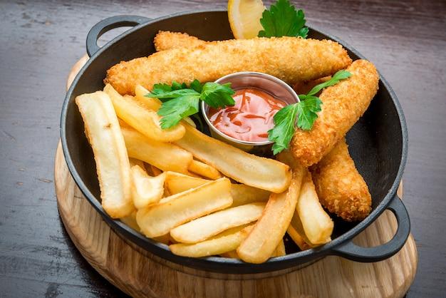 Vis met patat op houten lijst, smakelijk voedsel.