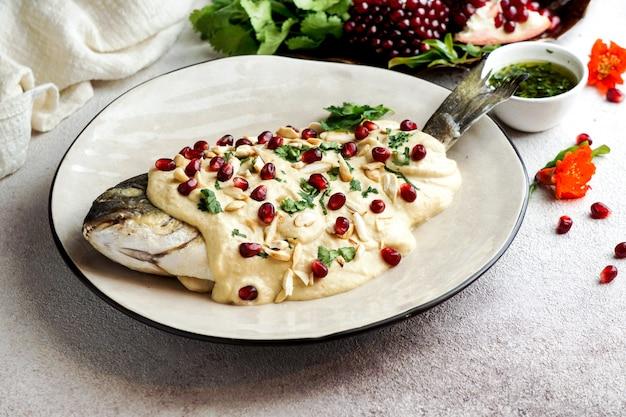 Vis met tahinisaus, granaatappelpitjes en amandel
