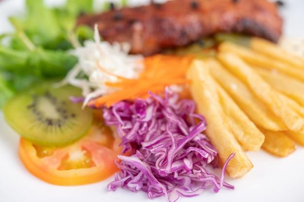 Vis steak met frietjes, kiwi, sla, wortelen, tomaten en kool in een witte schotel.