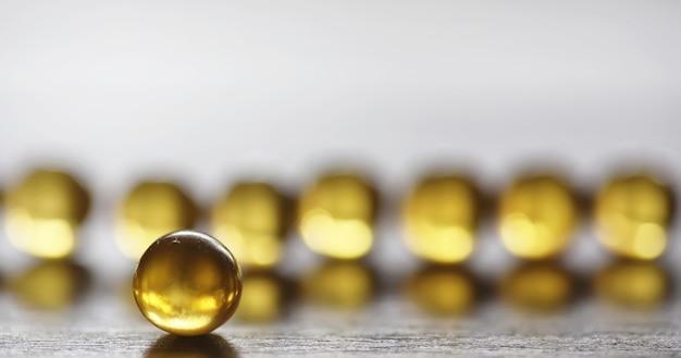 Vis vet. medische producten voor de behandeling van ziekten. het concept van gezondheidsafhankelijkheid van tablets. capsules van visolie op houten achtergrond.