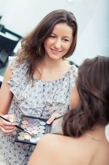 Visagist aan het werk met oogschaduwpalet en penseel, kleur kiezen, naar model kijken