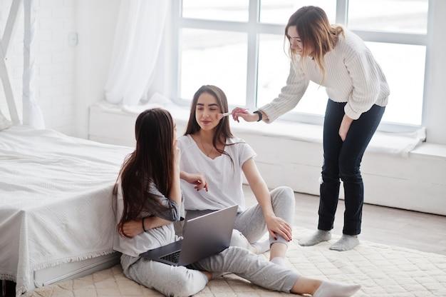 Visagist bereidt twee tweelingmodellen met laptop voor op studio voor fotoshoot.