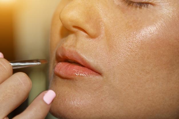 Visagist brengt roze lippenstift glans aan. mooi vrouwelijk gezicht. hand van een make-up meester schilderij lippen van een jong meisje schoonheid model. make-up bezig.