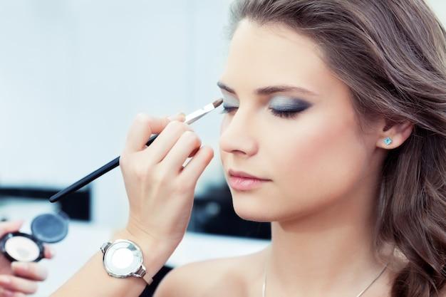 Visagist die basiskleur oogschaduw toepast op het oog van het model