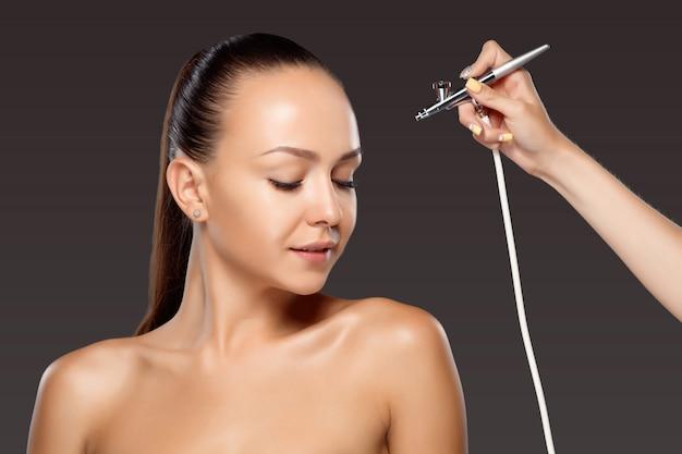Visagist die make-up voor model met aerograaf maakt