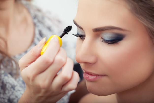 Visagist die mascara aanbrengt op de wimpers van het model, close-up, selectieve focus op wimpers en borstel