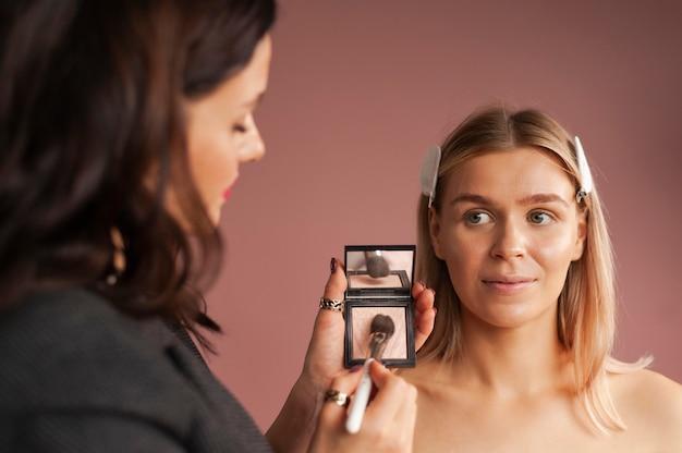 Visagist die met een blond model in een schoonheidssalon werkt