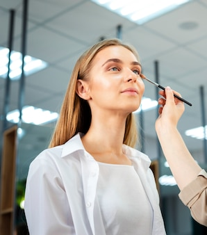Visagist die oogschaduw met borstel toepast