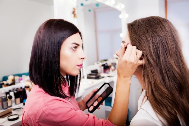 Visagist die oogschaduw op een vrouw toepast