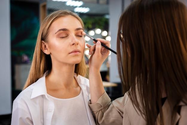 Visagist die oogschaduw op gezicht met borstel toepast