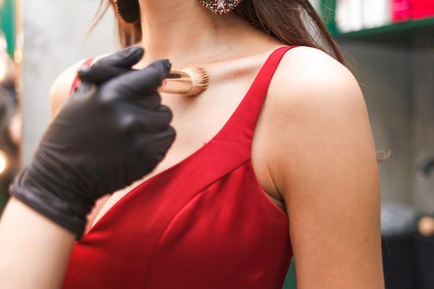 Visagist doet lichaamsmake-up met een poederborstel. dame in elegante avondjurk doet make-up in een schoonheidssalon