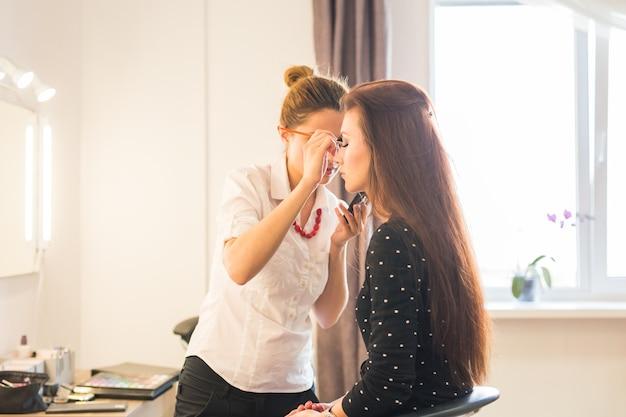 Visagist doet make-up mooi meisje in de salon, beauty concept en stijl.