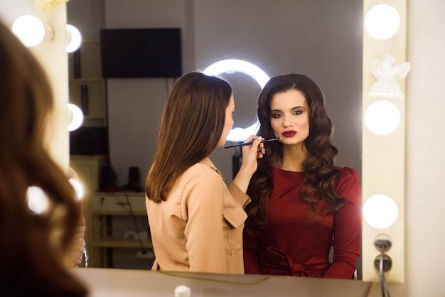 Visagist doet professionele make-up van jonge vrouw. school van visagisten.