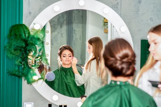 Visagist doet professionele make-up voor jonge vrouw in schoonheidssalon.