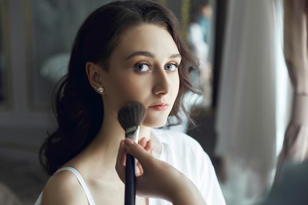 Visagist doet 's ochtends make-up voor een mooie vrouw.