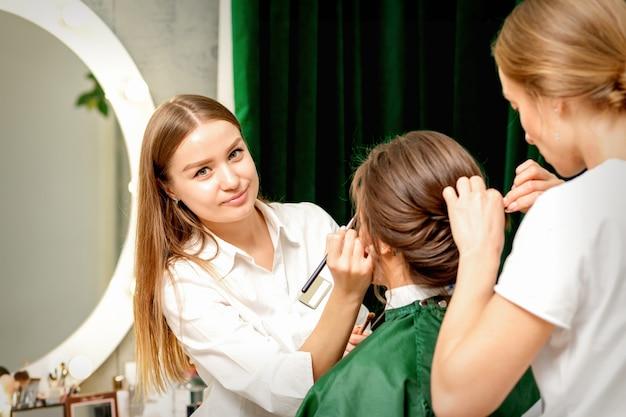 Visagist en kapper die met haar vrouwelijke cliënt in een schoonheidssalon werken