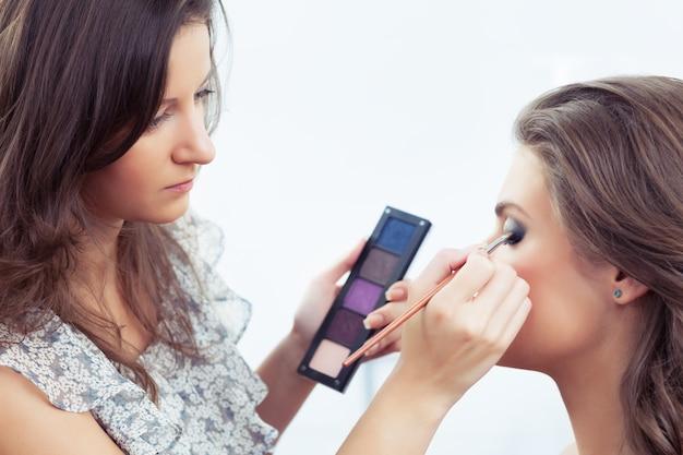 Visagist houdt oogschaduwpalet vast en past make-up toe, selectieve focus op het oog van het model