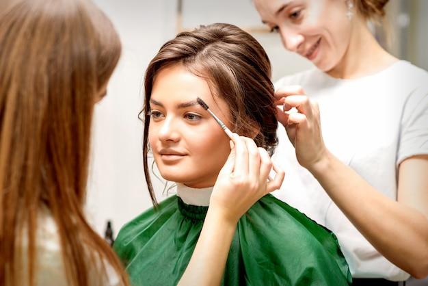 Visagist kammen wenkbrauwen en haarstylist kapsel voorbereiden op mooie jonge blanke bruid in een schoonheidssalon tandem van twee schoonheidsmeesters