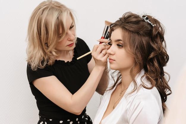 Visagist legt een penseelschaduw op de ogen van de bruid in een professionele schoonheidssalon