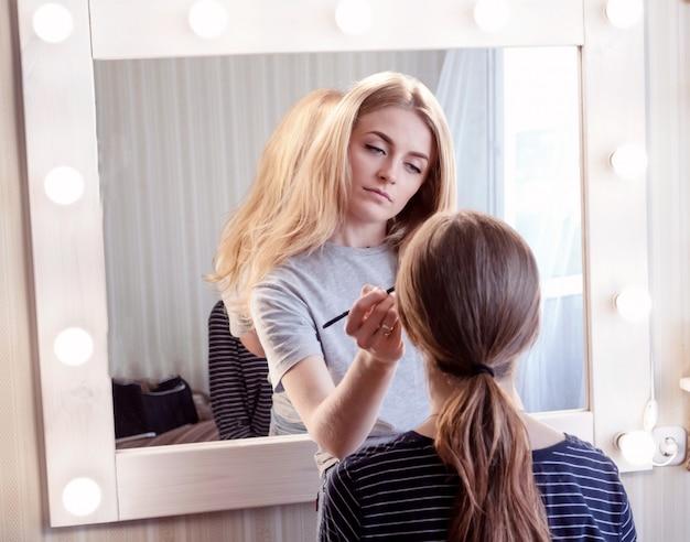 Visagist maakt avond make-up van jong meisje bruinharig. concept van schoonheid, huidverzorging, make-up.