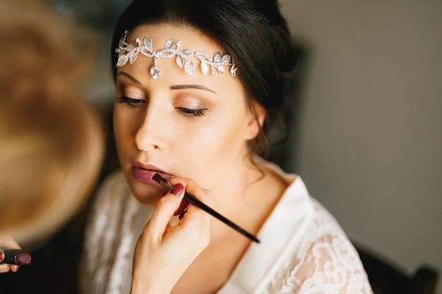 Visagist maakt make-up voor de bruid in een hotelkamer tijdens de voorbereiding op de huwelijksceremonie