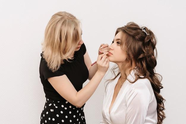 Visagist maakt professionele make-up voor een jonge bruid