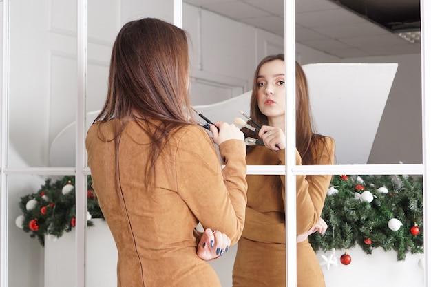 Visagist met lang donker haar met een poederborstel, hooghartige uitdrukking, reflectie in de spiegel, kerstdecor erachter