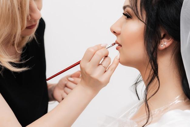 Visagist past lipgloss met een borstel toe op de lippen van de bruid van een meisje in een professionele schoonheidssalon