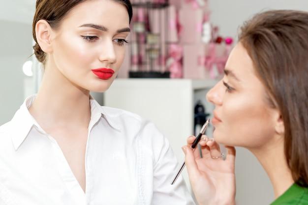 Visagist past lippenstift op mooie vrouw gezicht, make-up in proces.
