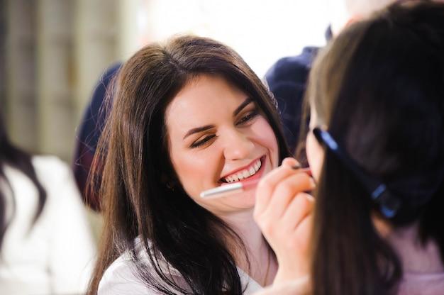 Visagist past lippenstift toe. mooi vrouwengezicht. perfecte make-up.