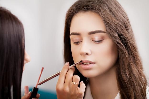 Visagist past make-up toe op aantrekkelijk blondemeisje bij de spiegel met lampen in de schoonheidssalon.