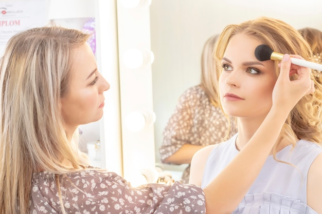 Visagist past modelmake-up toe op het gezicht. bruidsmake-up, lichte avondmake-up, in nude tinten