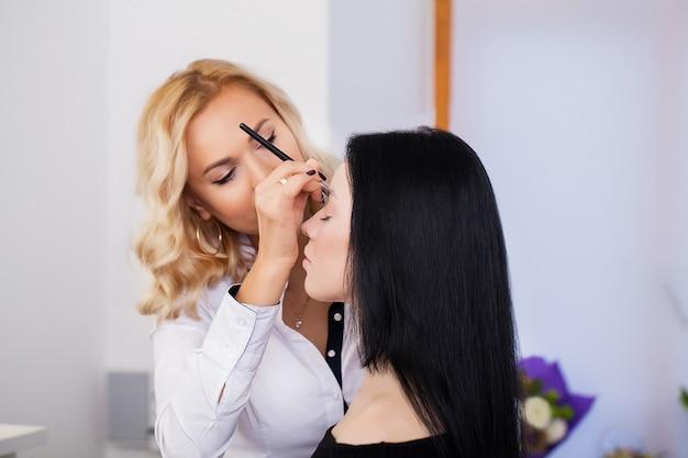 Visagist past oogschaduw toe. mooi vrouwengezicht. perfecte make-up