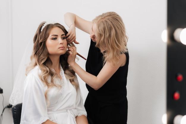 Visagist past poeder toe op het gezicht van de bruid van een meisje in een professionele schoonheidssalon
