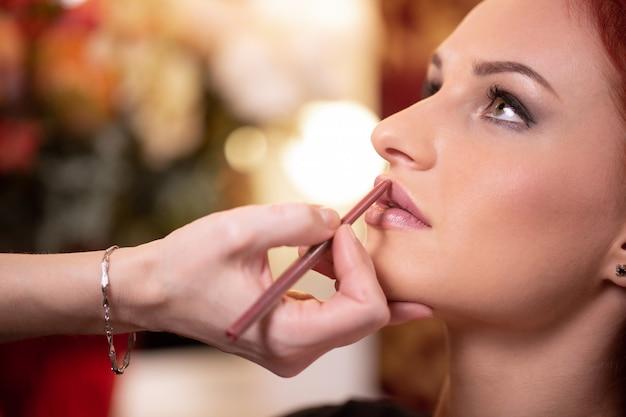Visagist past rode lippenstift toe. mooi vrouwengezicht. hand van make-up master, schilderij lippen van jonge schoonheid model meisje. make-up bezig
