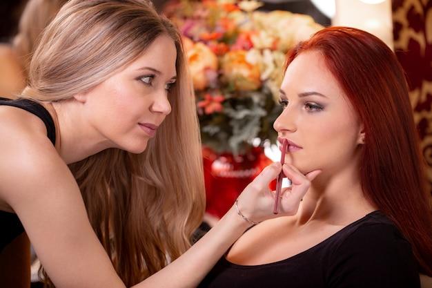 Visagist past rode lippenstift toe. mooi vrouwengezicht. hand van make-up meester, schilderij lippen van jonge schoonheid model meisje. make-up in proces