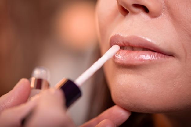 Visagist past rode lippenstift toe. mooi vrouwengezicht.