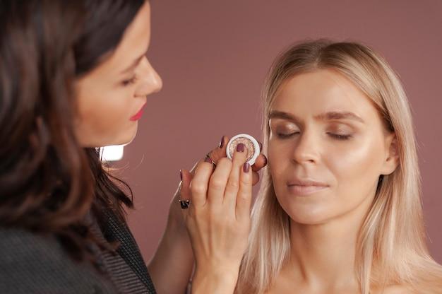 Visagist past vloeibare oogschaduw toe op het gezicht van een mooie vrouw
