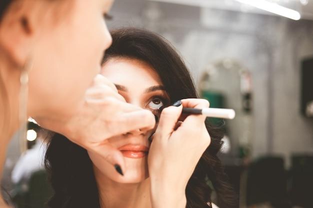 Visagist schildert ogen met eyeliner. professionele visagiste doet make-up op een mooie dame
