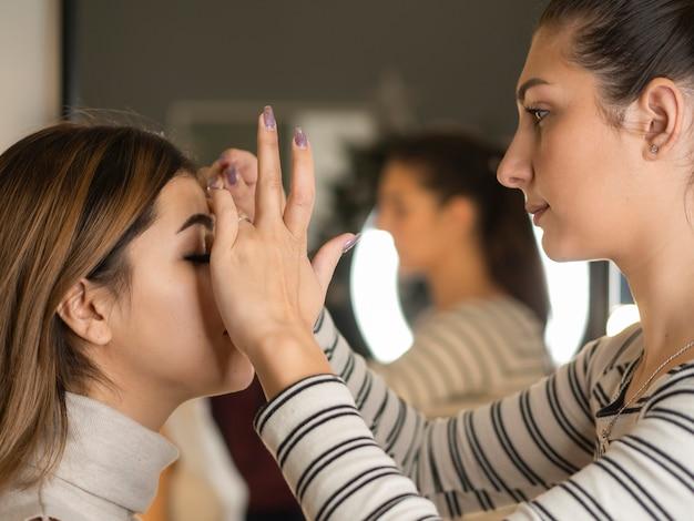 Visagist schildert wenkbrauw van een jonge vrouw met penseel in de buurt van spiegel
