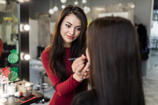 Visagist stelt voor om de kleur van lippenstift te veranderen in jong model met lang haar