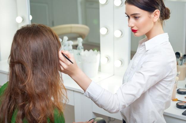 Visagist werkt met haar cliënt in de buurt van de spiegel in de schoonheidssalon