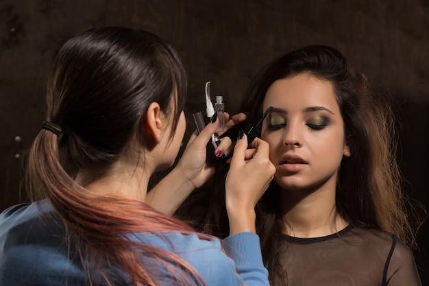 Visagist werkt met jong model in de studio