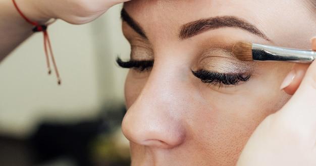 Visagist zet een penseelschaduw op de ogen van een vrouw in een schoonheidssalon